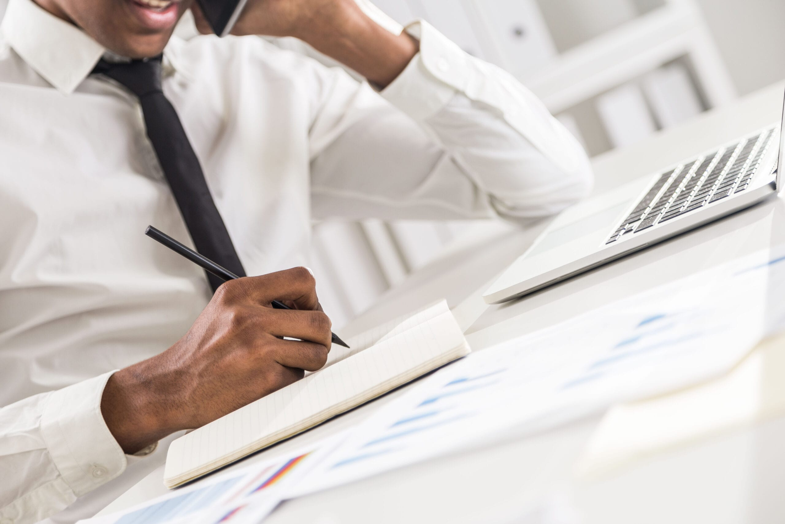 Side view of attractive african american businessman using notepad and notebook on office desktop while having mobile phone conversation. Bookshelf with documents in the background